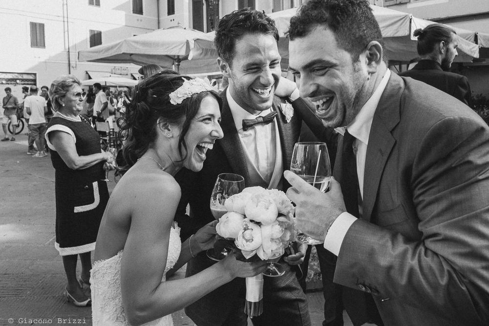 La sposa scherza con due amici durante l'aperitivo in piazza, fotografo matrimonio Forte dei Marmi, Versilia
