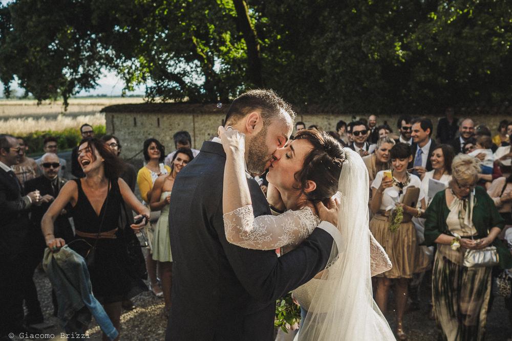 Bacio degli sposi fuori la chiesa matrimonio Castello di Paderna a Pontenure