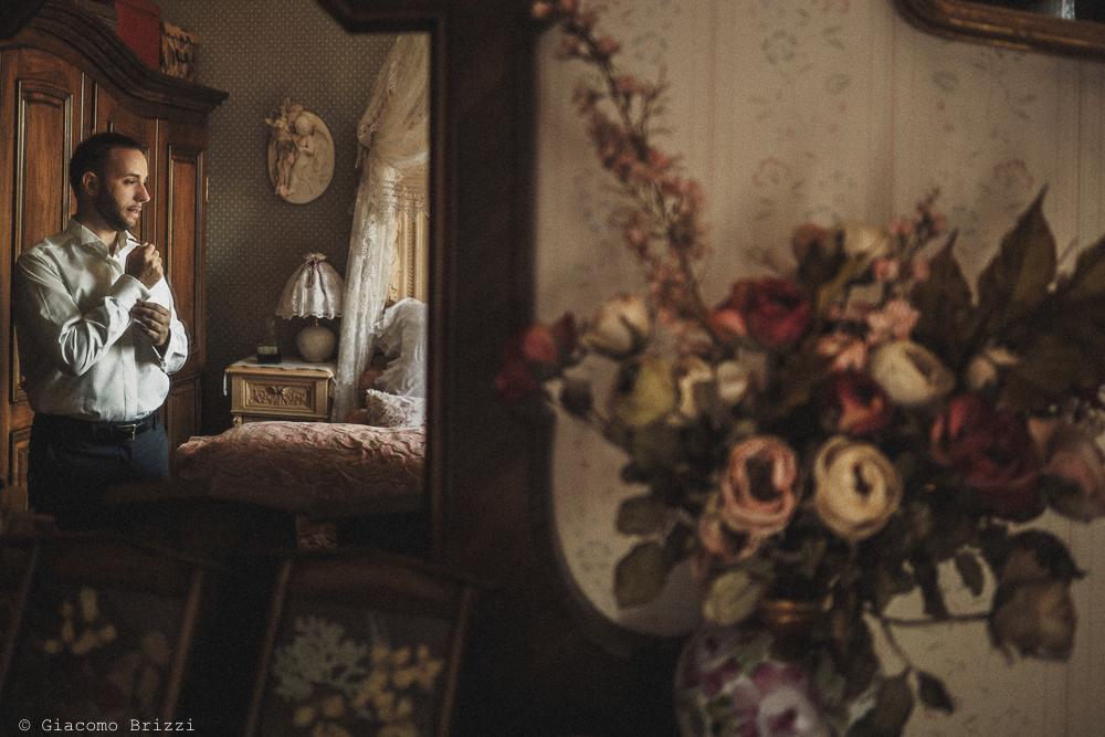 Lo sposo riflesso nello specchio fotografo matrimonio Castello di Paderna a Pontenure