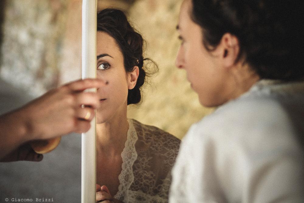 Foto di dettaglio della sposa riflessa nello specchio fotografo matrimonio Castello di Paderna a Pontenure