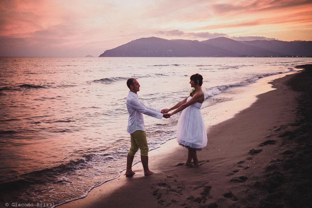 Gli sposi si tengono per mano in riva al mare, fotografo matrimonio Sarzana, Liguria