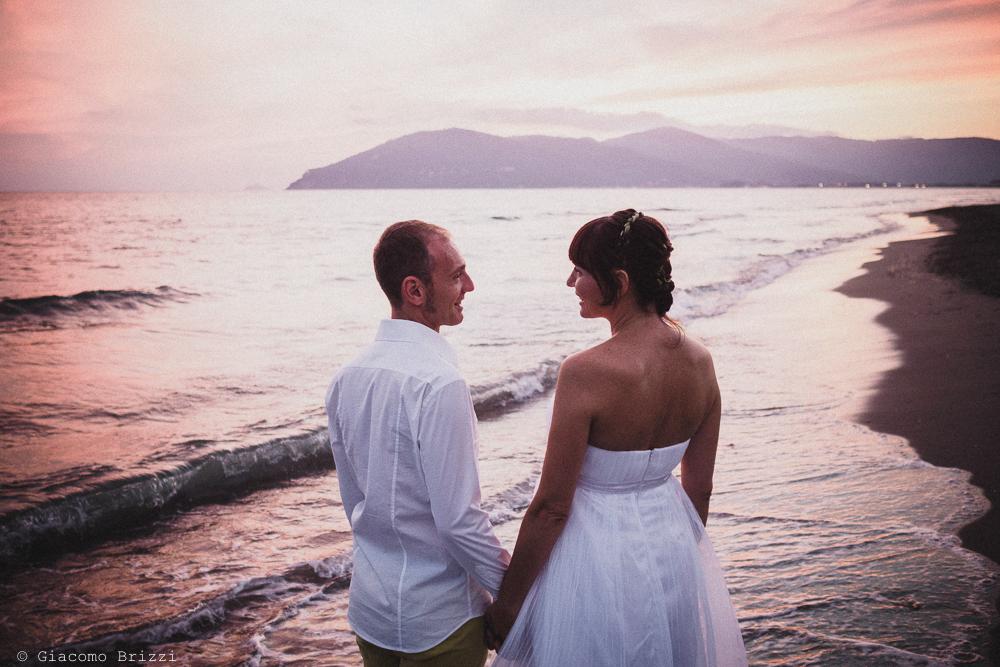 Gli sposi di spalle in riva al mare, fotografo matrimonio Sarzana, Liguria