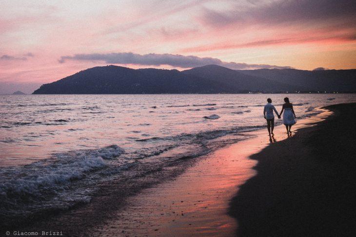 Gli sposi si allontanano lungo la riva del mare al tramonto, fotografo matrimonio Sarzana, Liguria