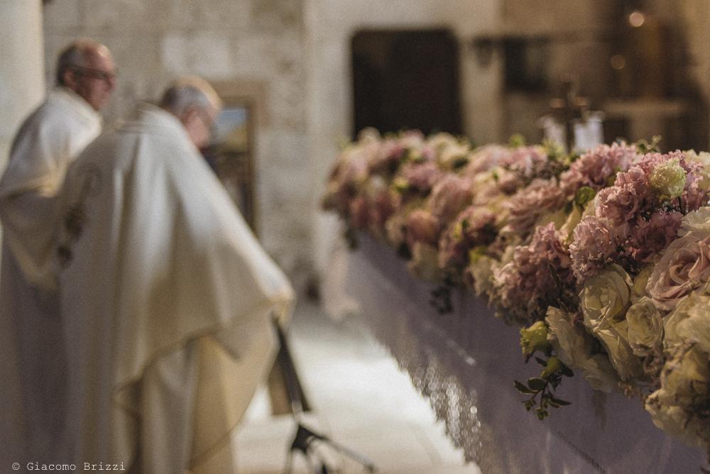 Foto di dettaglio sui fiori in chiesa e prete celebrante sullo sfondo, fotografo matrimonio pietrasanta versilia