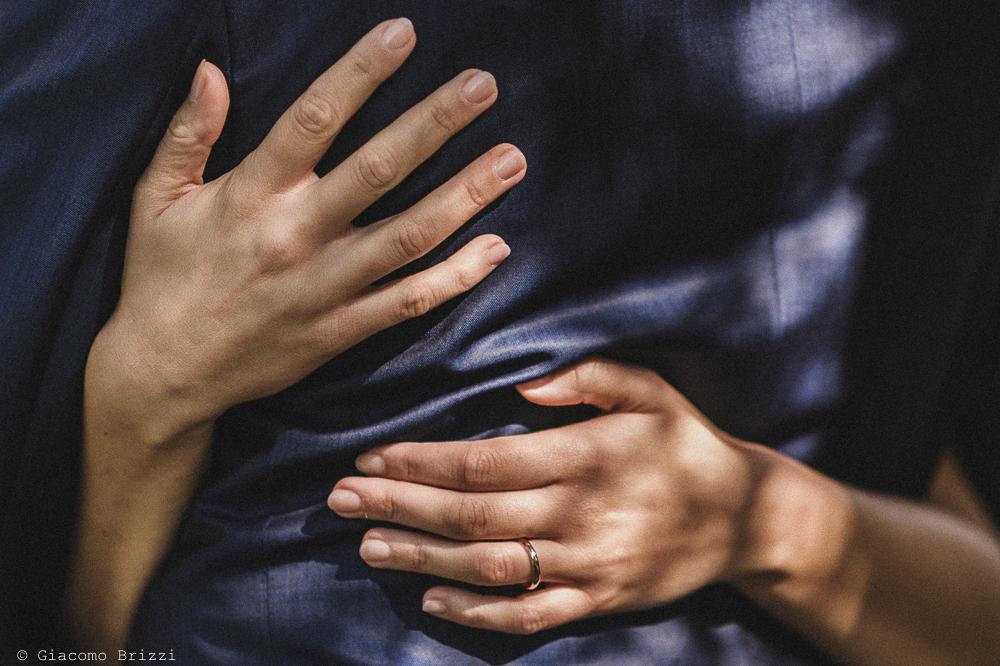 Inquadratura di dettaglio sulle mani della sposa che abbracciano lo sposo, fotografo matrimonio pietrasanta versilia