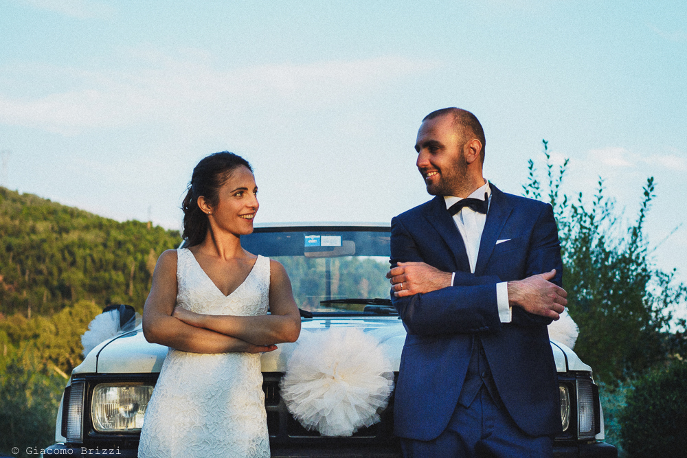 Foto simpatica ai due sposi appoggiati alla loro auto prima di partire, fotografo matrimonio pietrasanta versilia