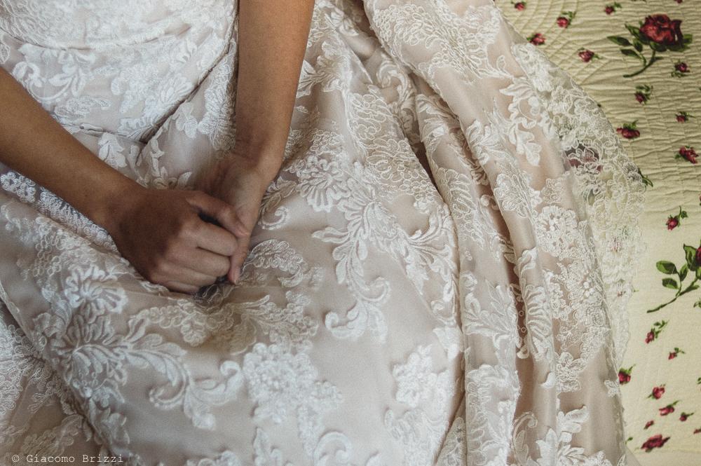 Foto di dettaglio sulle mani della sposa e l'abito, durante i preparativi, fotografo matrimonio pietrasanta versilia
