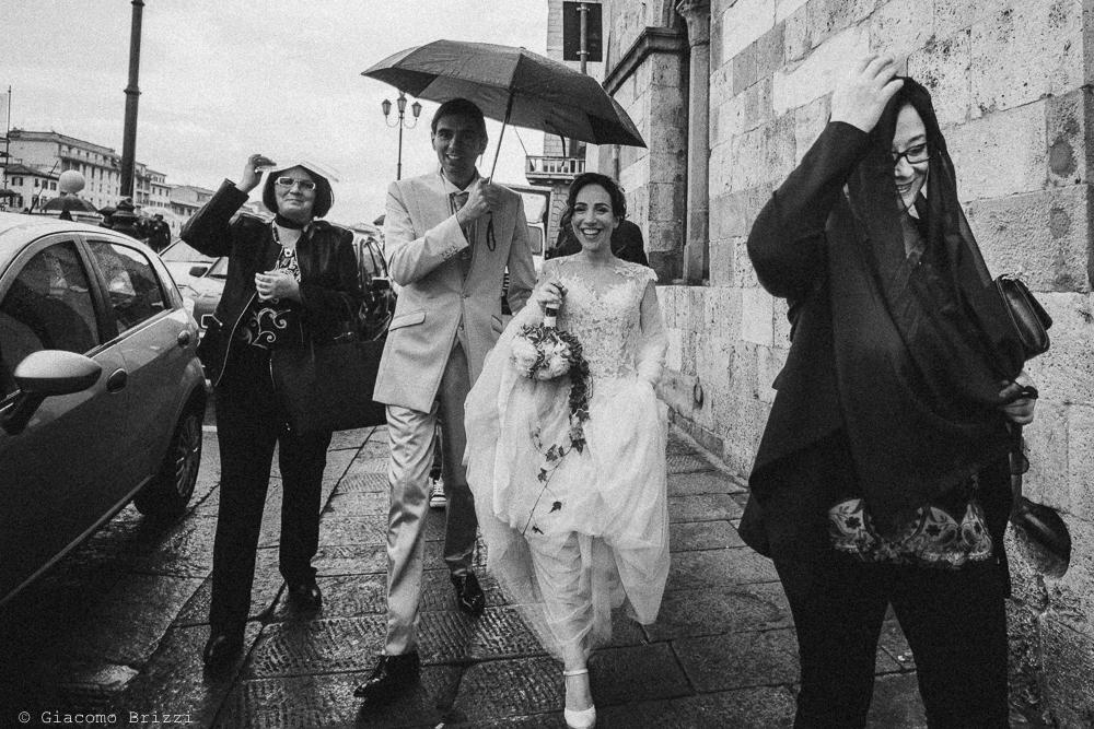 Gli sposi passeggiano sotto una leggera pioggerellina, fotografo ricevimento matrimonio a pisa, palazzo dei dodici