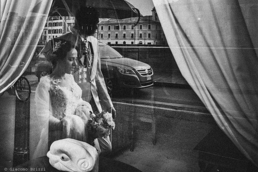 Gli sposi passeggiano ripresi nel riflesso di una vetrina, fotografo ricevimento matrimonio a pisa, palazzo dei dodici
