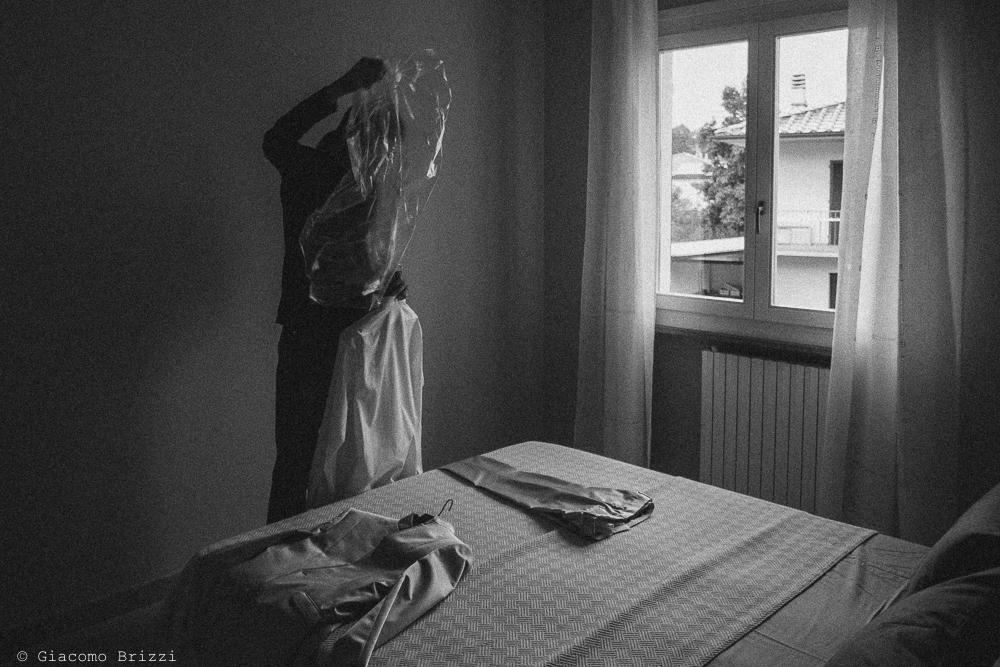 Foto artistica sullo sposo che prepara il suo abito, fotografo ricevimento matrimonio a pisa, palazzo dei dodici