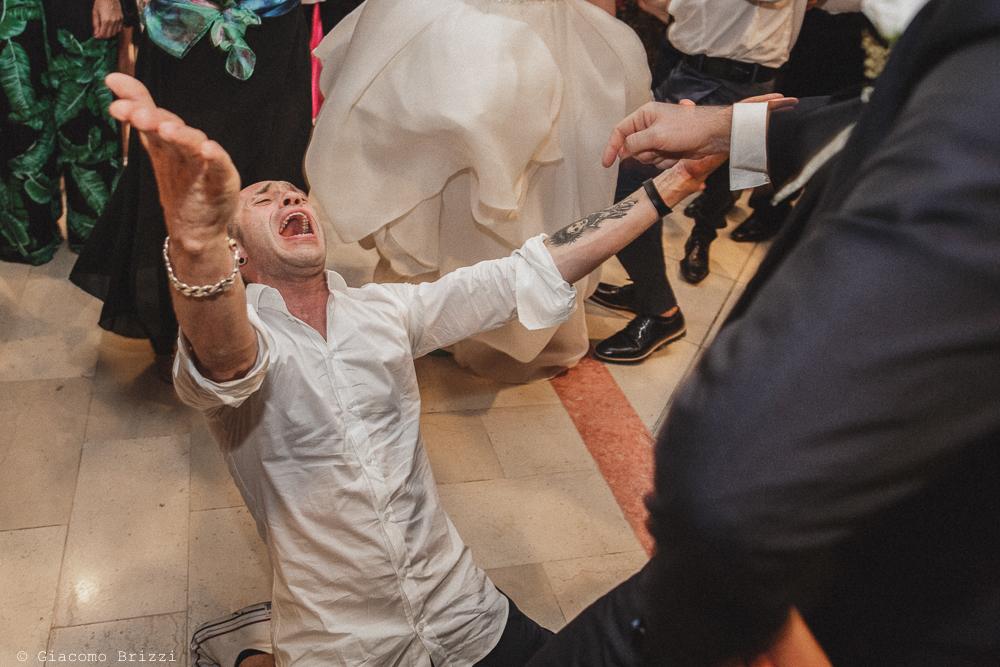 Un invitato mima una serenata, fotografo matrimonio francavilla fontana, puglia