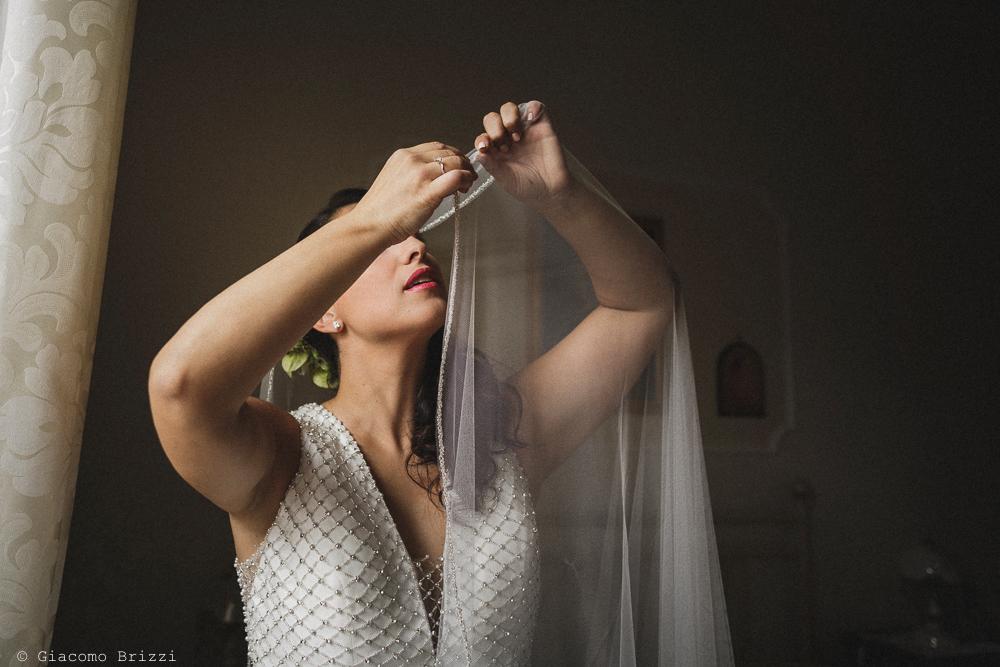 Foto della sposa che inizia ad indossare l'abito, fotografo matrimonio francavilla fontana, puglia