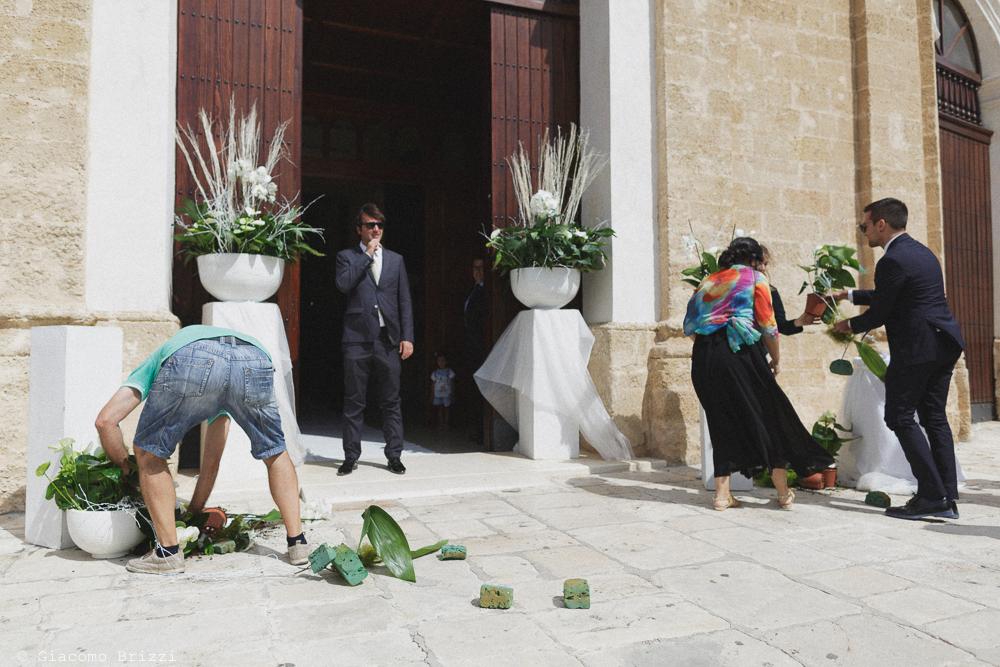 Ultimi preparativi ai fiori all'ingresso della chiesa, fotografo matrimonio francavilla fontana, puglia