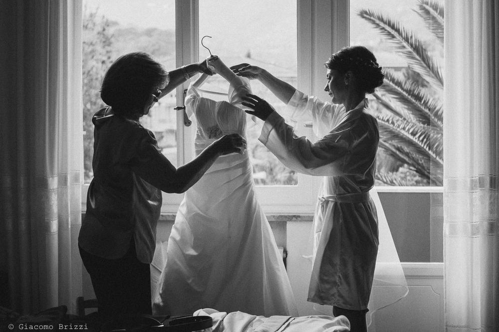 La sposa si accinge ad indossare l'abito, fotografo matrimonio rapallo, liguria