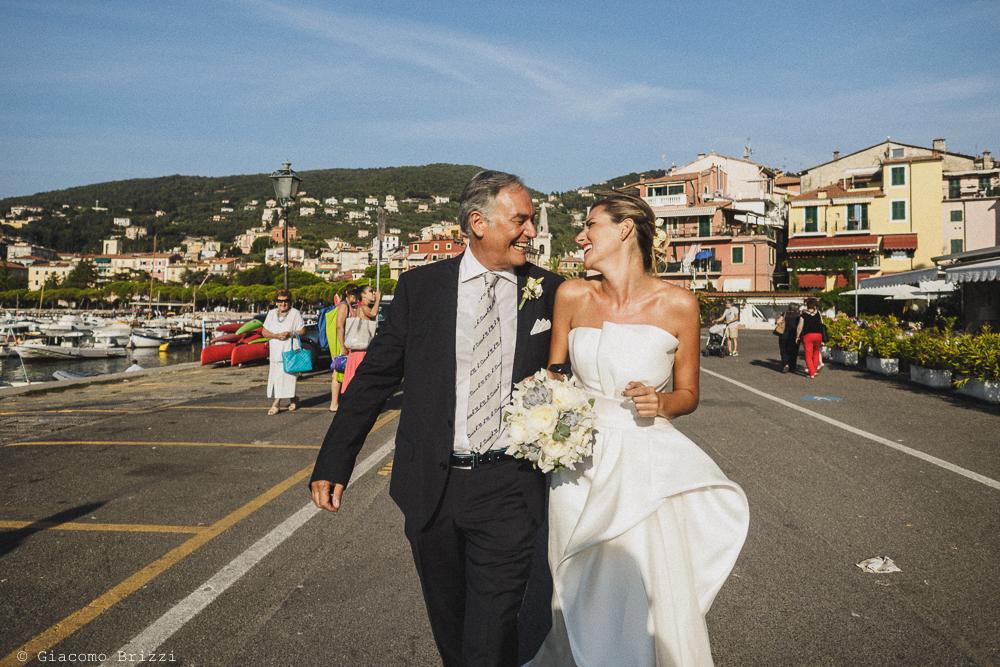 La sposa sorridente è accompagnata dal padre verso la cerimonia, fotografo matrimonio ricevimento castello di lerici