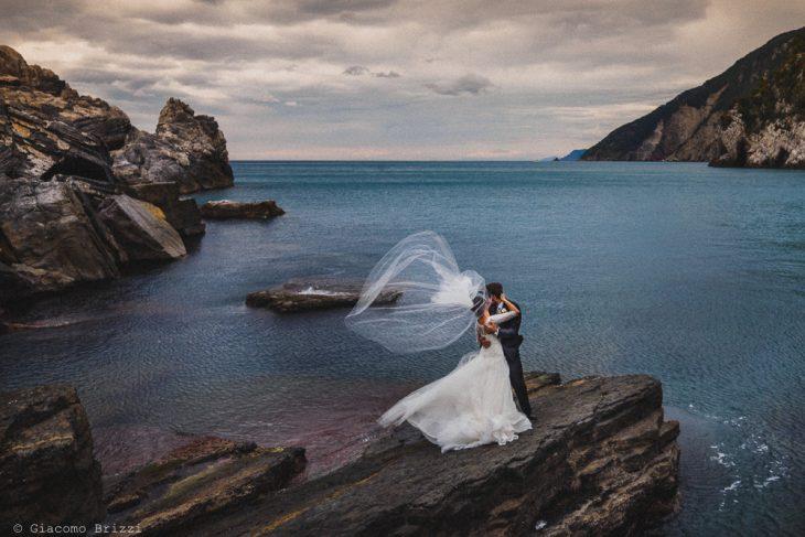 Gli sposi fotografati sugli scogli con il golfo ligure sullo sfondo, fotografo matrimonio ricevimento hotel europa, lerici