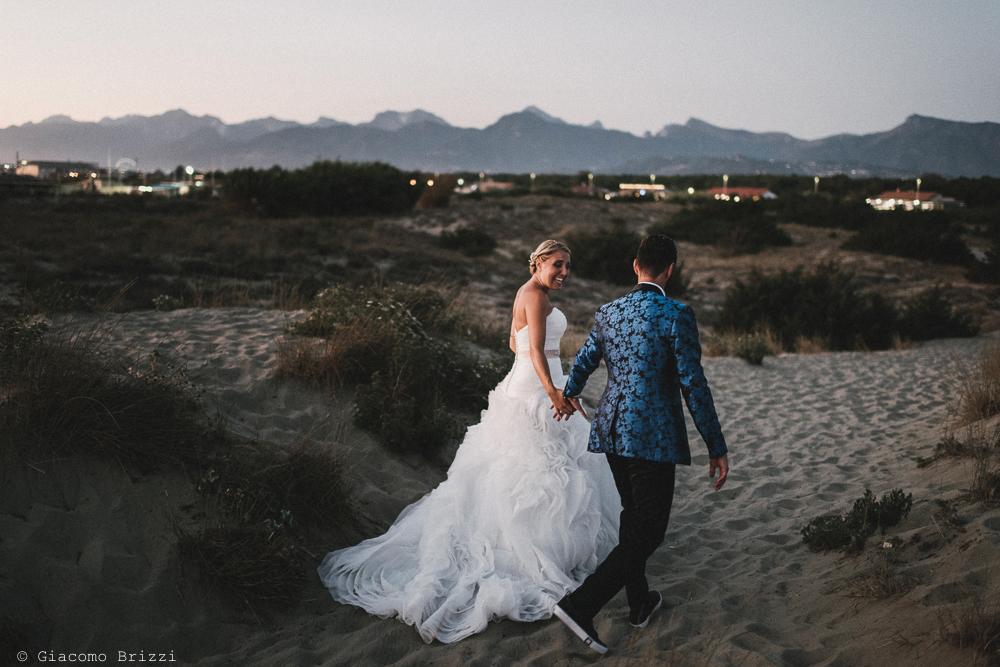 Gli sposi si allontanano mano nella mano matrimonio viareggio la costa dei barbari