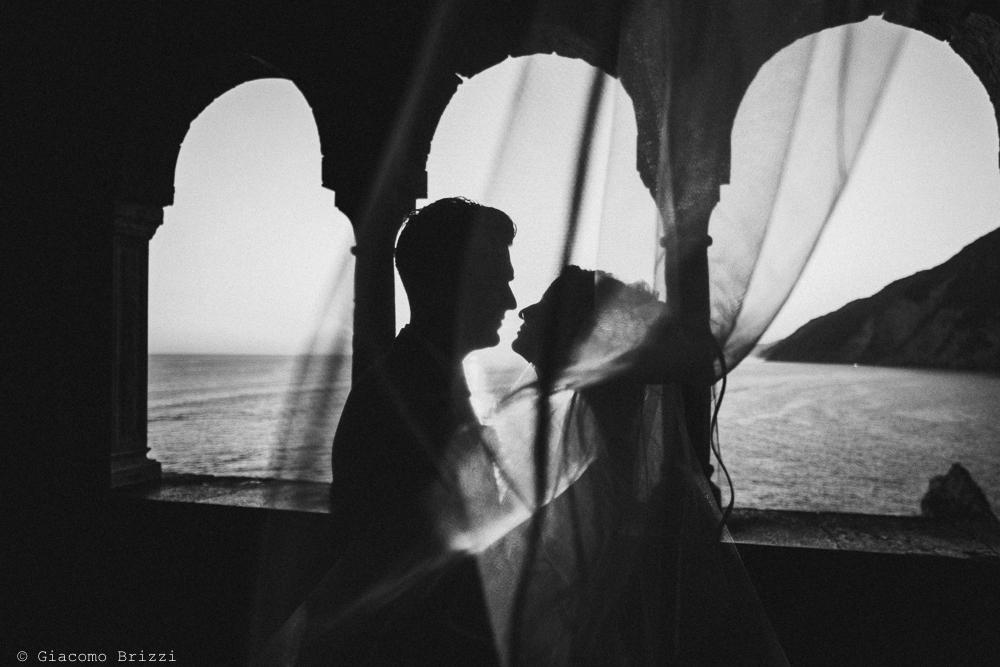 Foto in controluce degli sposi sotto i portici, fotografo matrimonio ricevimento le terrazze, portovenere