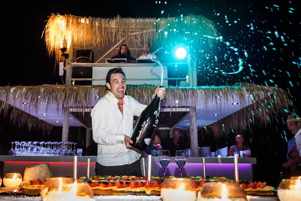 Lo sposo stappa e festeggia con una bottiglia di champagne, fotografo matrimonio ricevimento Sunset, Forte dei Marmi