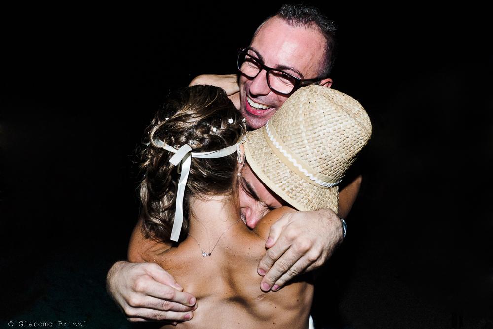 Un abbraccio alla sposa, fotografo matrimonio ricevimento Sunset, Forte dei Marmi