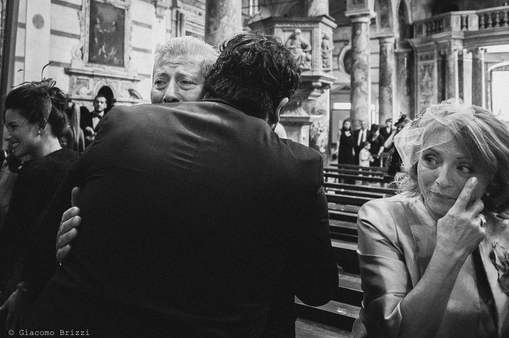 Abbraccio commovente con lo sposo, fotografo matrimonio ricevimento villa fanini, Lucca