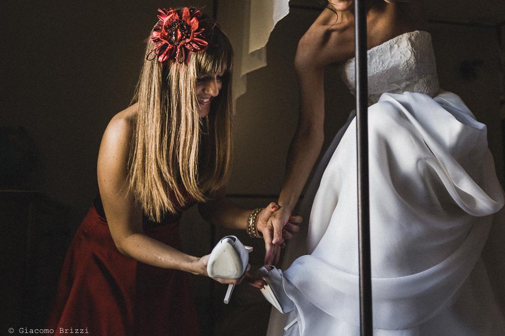 La sposa calza le scarpe, nella preparazione per il matrimonio, fotografo matrimonio ricevimento villa fanini, Lucca