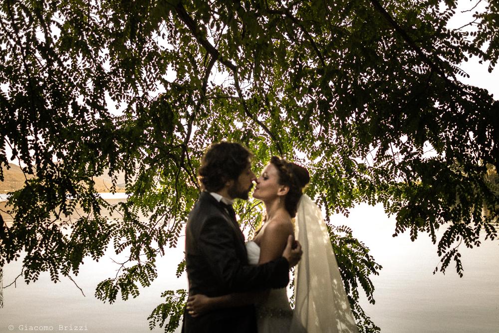 Ritratto in controluce, bacio tra gli sposi, fotografo matrimonio ricevimento Villa Orlando, Versilia