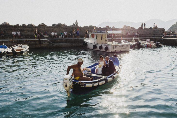 I due sposi in barchetta guidata da un pescatore, fotografo matrimonio Vernazza, Cinque Terre