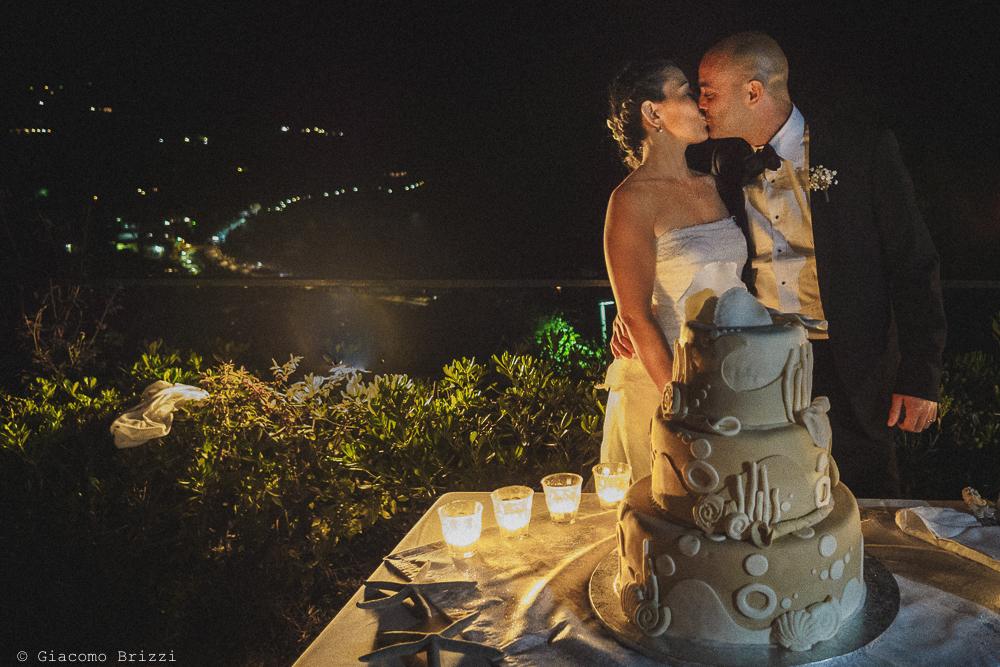 Il bacio dei due sposi con sullo sfondo l'affascinante Golfo illuminato con le luci della sera, fotografo matrimonio Vernazza, Cinque Terre