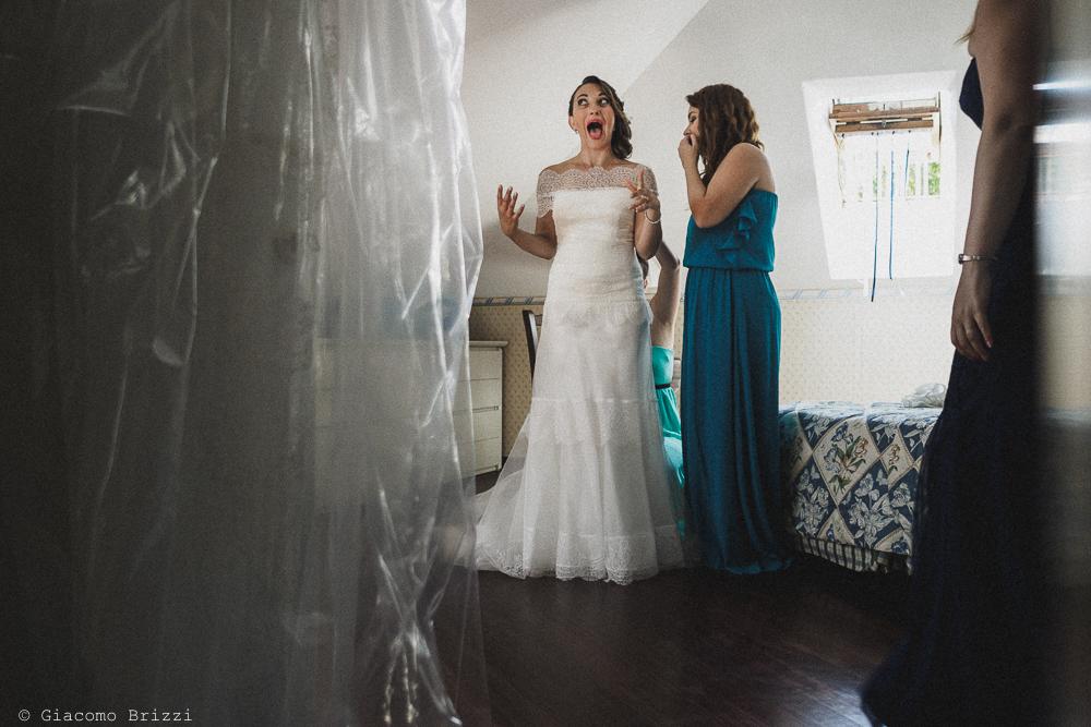 Un inquadratura della sposa con espressione esilarante, mentre indossa il vestito, fotografo matrimonio Vernazza, Cinque Terre