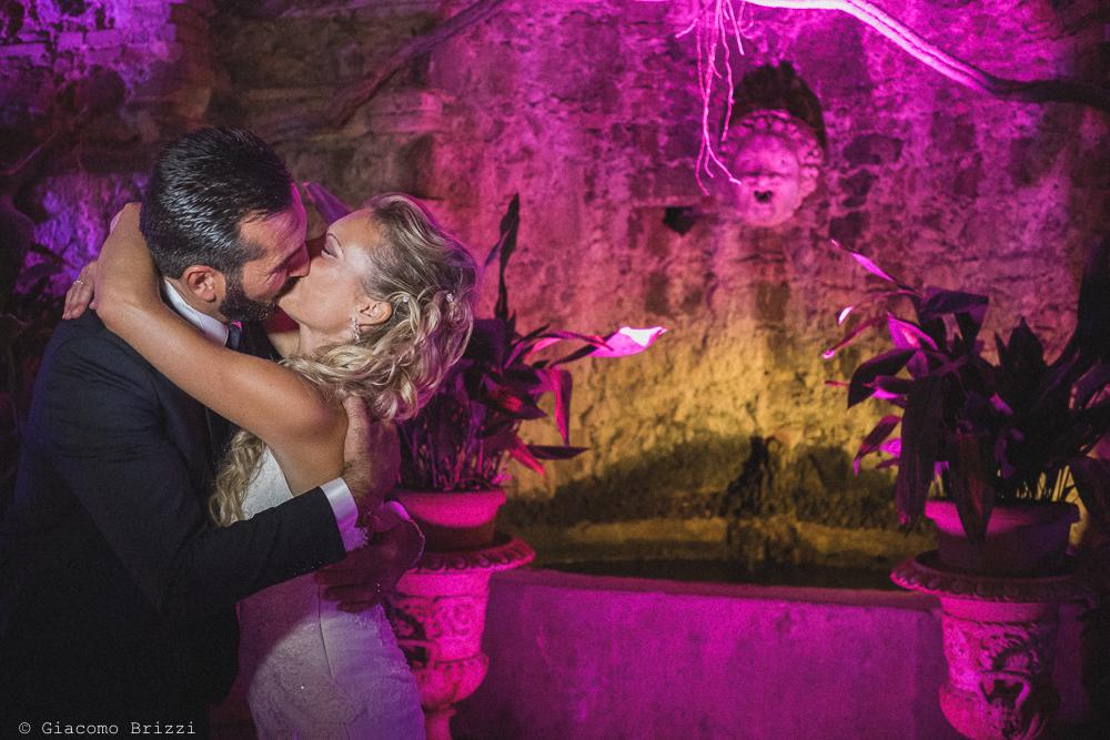 Il bacio degli sposi con sullo sfondo la scenografica location, fotografo ricevimento villa grabau, lucca