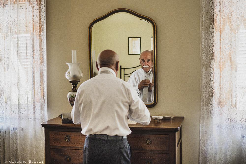 Il padre controlla gli ultimi dettagli al suo vestito, fotografo ricevimento villa grabau, lucca