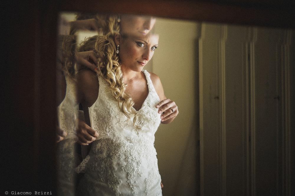 Sposa riflessa nello specchio verifica i dettagli del suo abito, fotografo ricevimento villa grabau, lucca