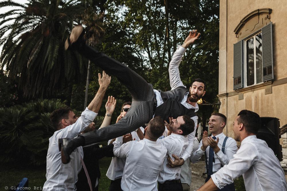 Gli invitati lanciano lo sposo in aria, matrimonio San Giuliano Terme, Pisa. Giacomo Brizzi Fotografo