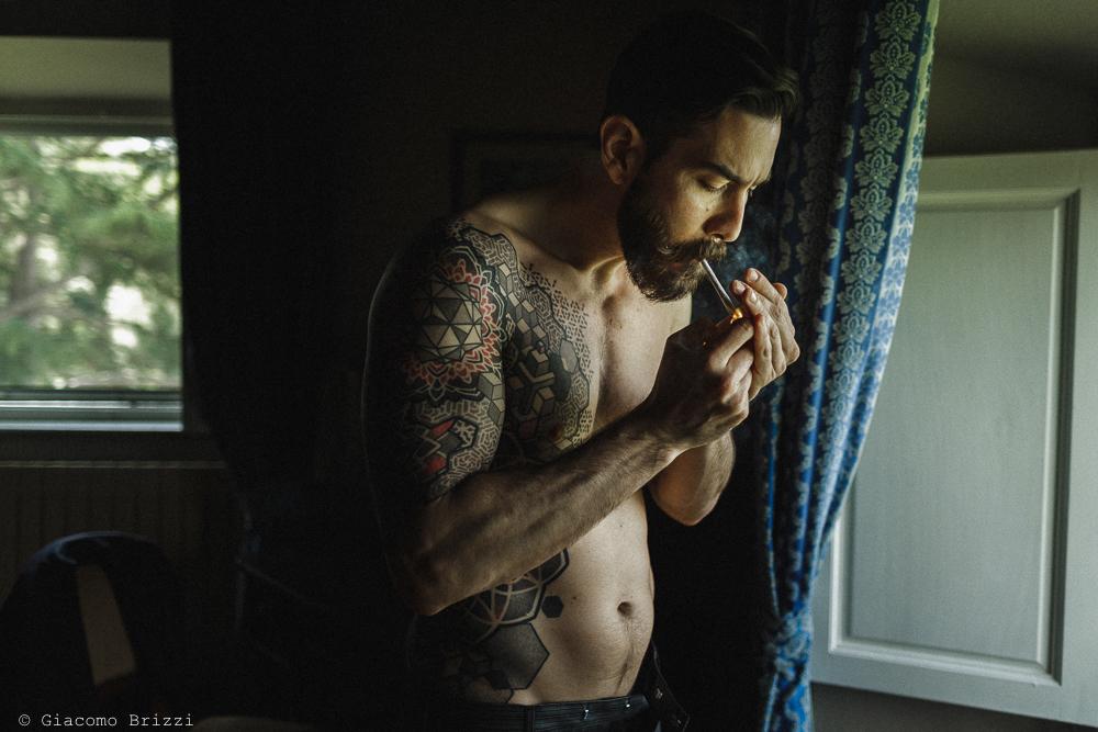 Uomo accende una sigaretta, matrimonio San Giuliano Terme, Pisa. Giacomo Brizzi Fotografo